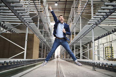 Excited businessman jumping in factory - BSZF01207