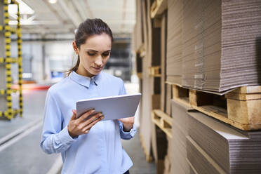 Businesswoman using tablet in a factory warehouse - BSZF01228