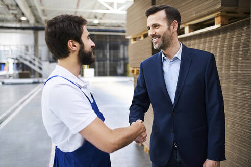 Businessman and worker shaking hands in a factory - BSZF01240