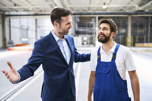 Happy businessman and worker in a factory - BSZF01243