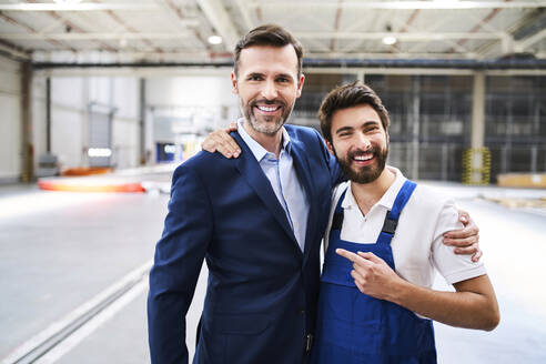 Portrait of happy businessman and worker in a factory - BSZF01246