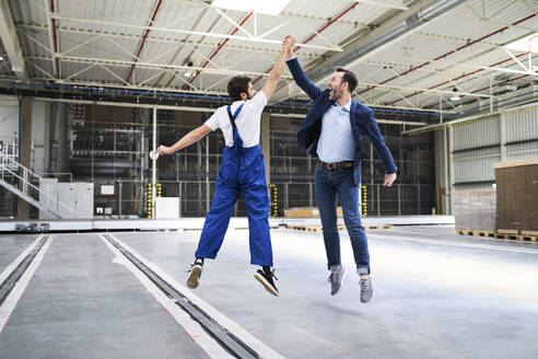 Excited businessman and worker jumping and high fiving in a factory - BSZF01249