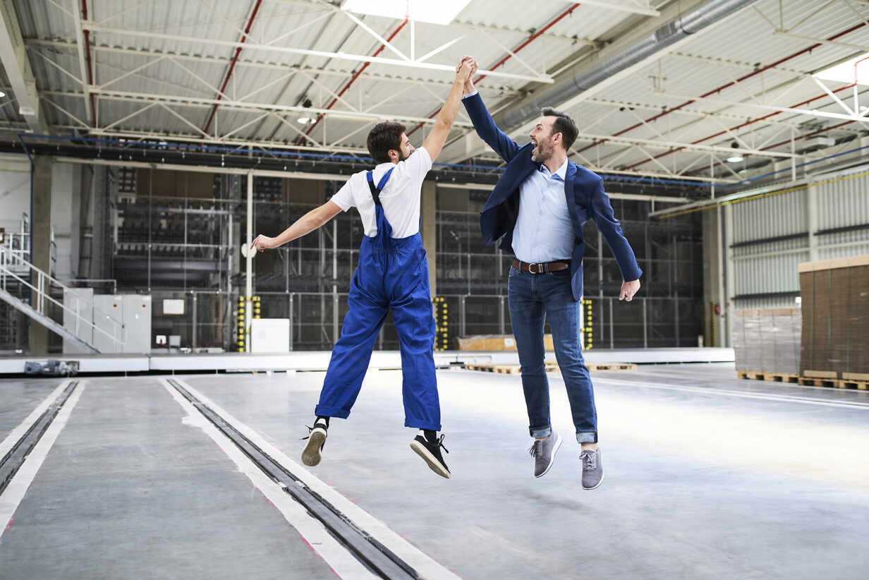Excited businessman and worker jumping and high fiving in a factory - BSZF01249 - Bartek Szewczyk/Westend61