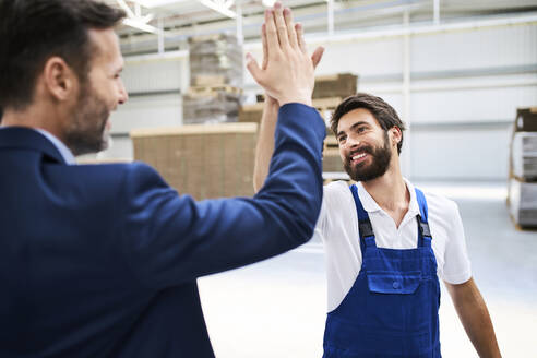 Happy businessman and worker high fiving in a factory - BSZF01252