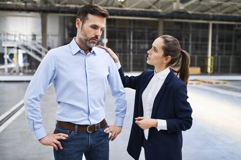 Businesswoman talking to disappointed businessman in a factory - BSZF01255