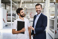 Portrait of smiling businessman and employee with clipboard in a factory - BSZF01267