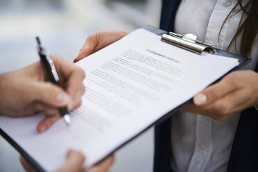 Close-up of employee signing employment contract - BSZF01270