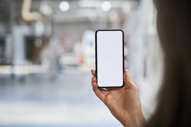 Close-up of businesswoman holding cell phone in factory - BSZF01273