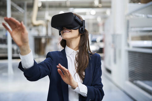 Businesswoman wearing VR glasses in factory - BSZF01276