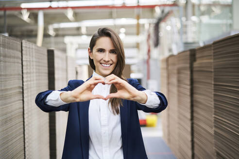 Portrait of happy businesswoman in factory warehouse shaping a heart with her hands - BSZF01285