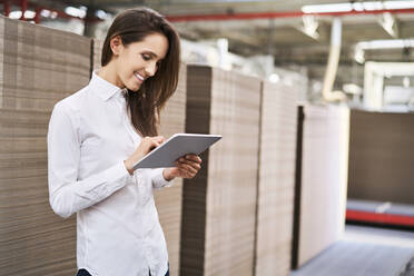Smiling young woman using tablet in a factory warehouse - BSZF01294