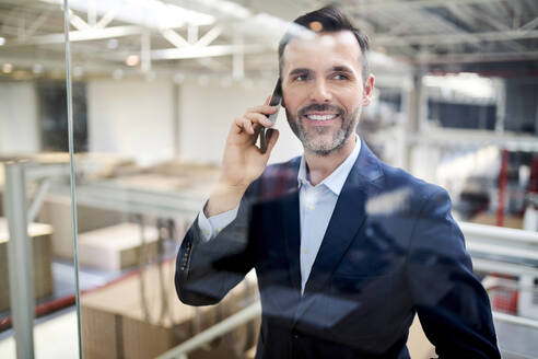 Portrait of smiling businessman on cell phone behind glass pane in a factory - BSZF01303