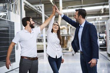 Happy businessman and employees high fiving in a factory - BSZF01312