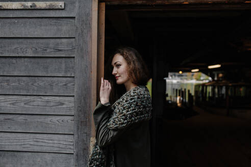 Portrait of redheaded woman at entrance of a boat house, looking sideways - OGF00085
