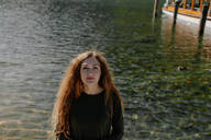Portrait of redheaded woman looking at camera, standing on lakeside - OGF00088