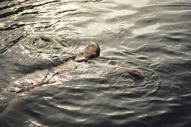 Young woman floating in water, relaxing in summer - GUSF02301