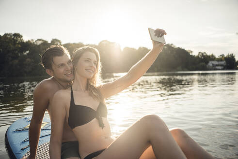 Happy couple sitting on paddleboard on a lake, taking smartphone selfies - GUSF02313