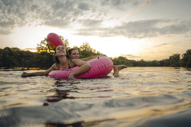 Friends having fun on a lake on a pink flamingo floating tire - GUSF02325