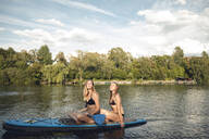 Girlfriends taking a sunbath on a paddleboard on the lake - GUSF02340