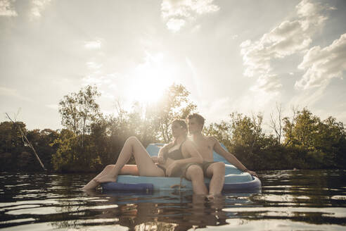 Young couple sitting on a boat on the lake, relaxing - GUSF02343
