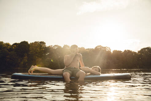 Youple on the lake, relaxing on a paddleboard, man talking on the phone - GUSF02349