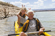 Older Caucasian man posing in kayak with granddaughter - BLEF13026