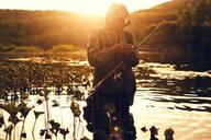 Mari fisherman preparing hook in lake - BLEF13056