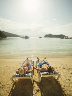 Caucasian couple holding hands in deck chairs on beach - BLEF13116