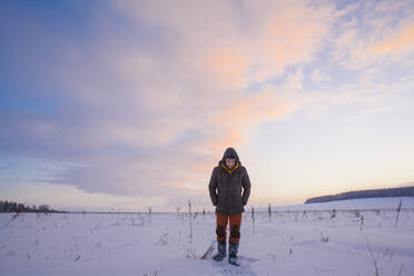 Mixed race man walking in snowy field - BLEF13387