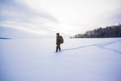 Mixed race man walking in snowy field - BLEF13396