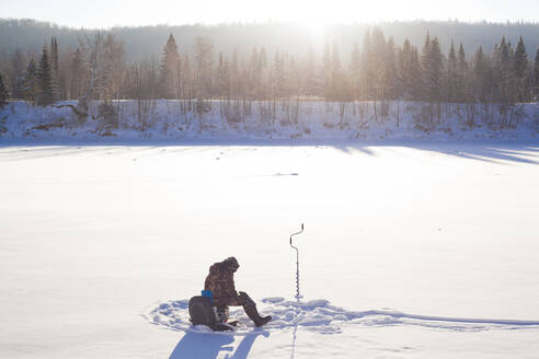 Mari man ice fishing in snowy field - BLEF13408