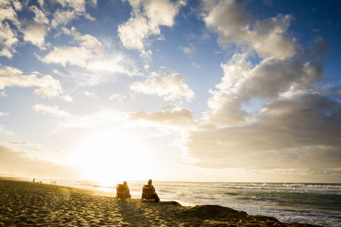People relaxing on beach at sunrise - BLEF13429