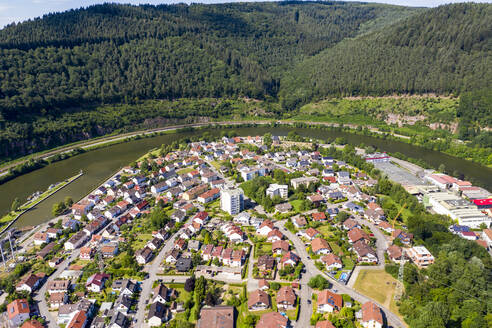Aerial view of houses by river and mountains during sunny day, Hesse, Germany - AMF07235
