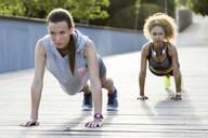 Two sporty young women doing push-ups on a bridge - JSRF00496