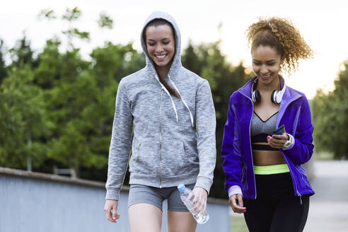 Two smiling sporty young women walking in park after workout - JSRF00502
