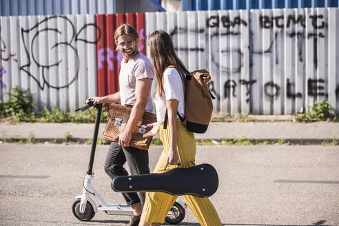 Young couple with electric scooter walking on the street - UUF18390