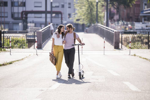 Happy young couple with electric scooter walking on the street - UUF18399