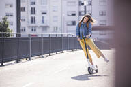 Happy young woman riding electric scooter on a bridge - UUF18408