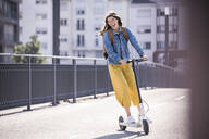 Happy young woman riding electric scooter on a bridge - UUF18411