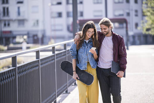 Young couple with skateboard and smartphone walking on a bridge - UUF18414