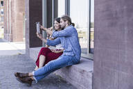 Young couple sitting on windowsill at a building using a tablet - UUF18423
