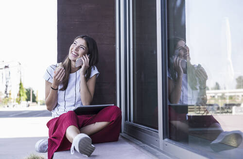 Young woman sitting on windowsill at a building talking on cell phone - UUF18429