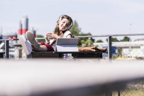 Young woman relaxing in a beer garden with headphones and tablet - UUF18450