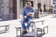 Young man sitting on table in a beer garden with headphones and tablet - UUF18453
