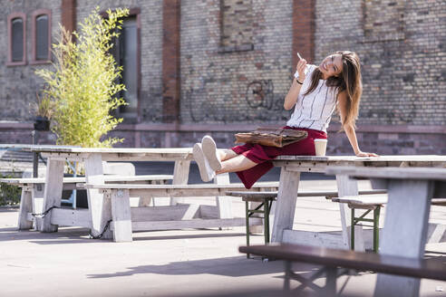 Young woman sitting on table in a beer garden using cell phone - UUF18459