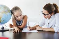Teacher helping schoolgirl at desk writing on paper - LJF00566
