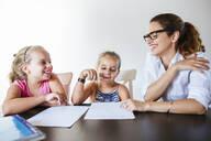 Happy teacher sitting at desk with two schoolgirls - LJF00575