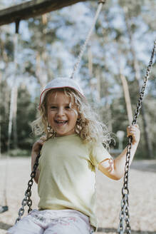 Portrait of happy girl on swing on a playground - DWF00461