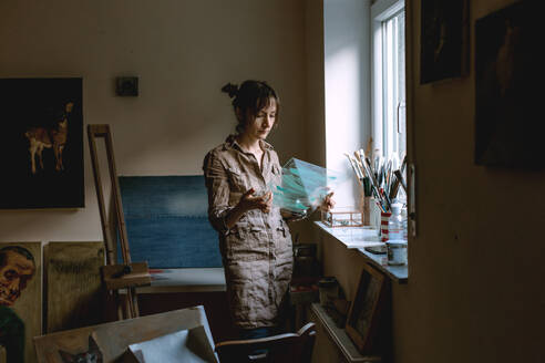Female artist holding glass pane in her studio - OGF00097