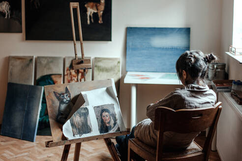 Rear view of a female artist sitting in her studio in front of a painting - OGF00100